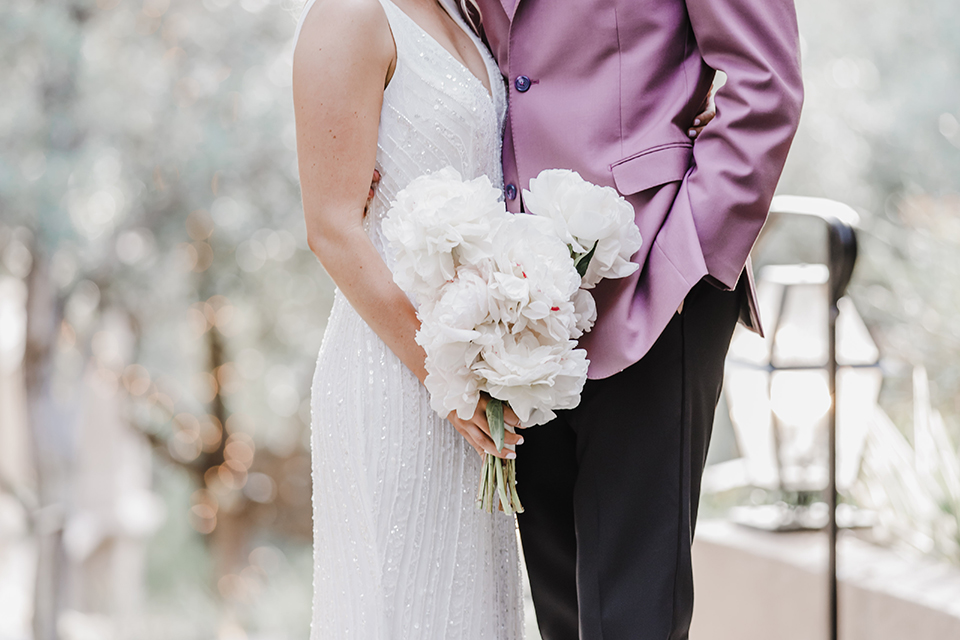 the bride and groom at the reception – the bride in a white lace gown and the groom in a rose pink coat and black pants