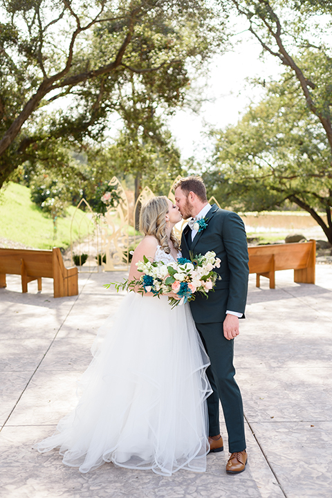 the bride in a white full ball gown with straps and the groom in a grey asphalt suit with a grey bow tie