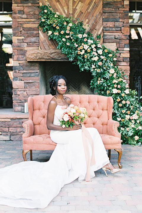 red rocks caramel wedding couple sitting – bride in a strapless modern gown and the groom in a caramel tan suit with a chocolate brown tie