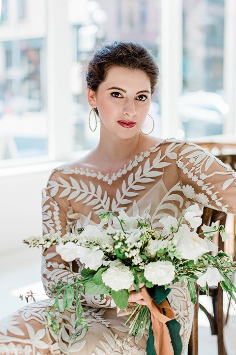 bride in an ivory lace gown with modern style design and a high neckline and long sleeves,