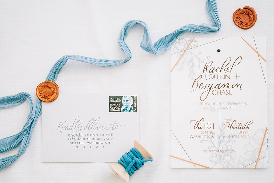 white invitations with a blue velvet linen and rings