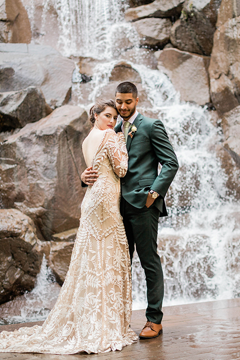 bride in an ivory lace gown with modern style design and a high neckline and long sleeves, the groom in a dark green suit with a black and white plaid tie
