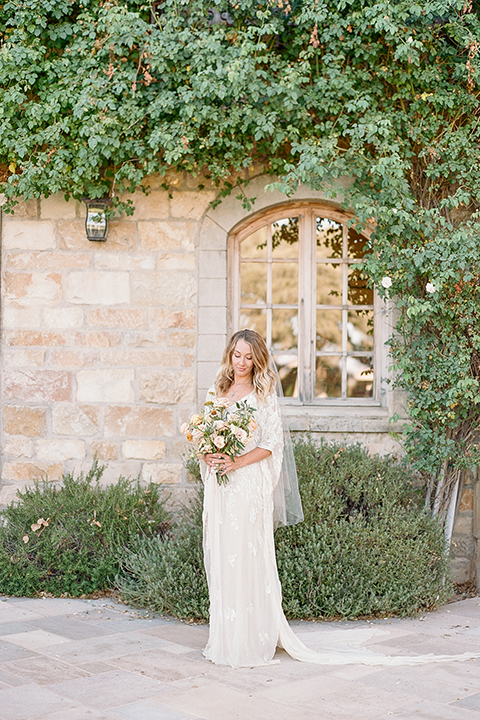 the bride in a lace flowing gown with bell sleeves
