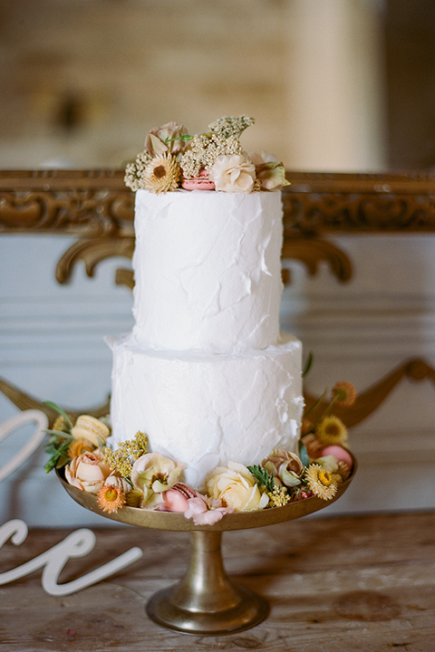white tiered cake with yellow and pink flowers