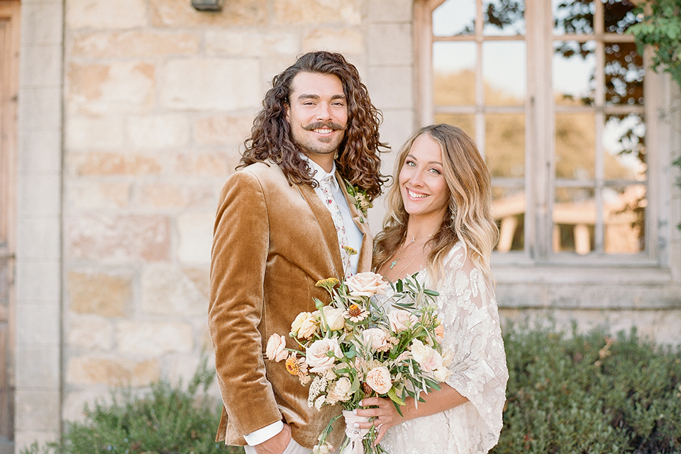 the bride in a lace flowing gown with bell sleeves and the groom in a gold velvet tuxedo